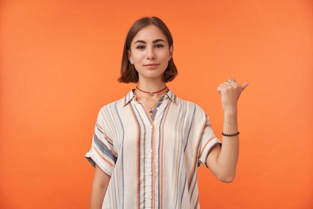 Portret ładnie wyglądającej dziewczyny, wskazując w prawo na sobie koszulę w paski, naszyjnik, bransoletki i pierścionki