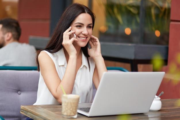 Portret ładnie wyglądającej kobiety przedsiębiorcy lubi komunikację przez telefon komórkowy, ma przyjemny uśmiech, koncentruje się gdzieś, korzysta z nowoczesnego laptopa, spędza wolny czas w przytulnej kawiarni.