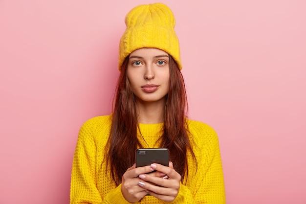 Portret ładnie wyglądającej kobiety wygląda poważnie, używa nowoczesnego telefonu komórkowego, nosi żółtą czapkę i zimowy sweter, pozuje na różowym tle, nie nosi makijażu