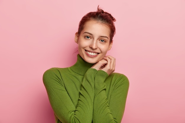 Portret ładnie wyglądającej młodej kobiety z zębatym uśmiechem, trzymająca dłonie przy policzku, ubrana w luźny poloneck, patrzy radośnie, cieszy się dobrą nowiną, pozuje na różowym tle.