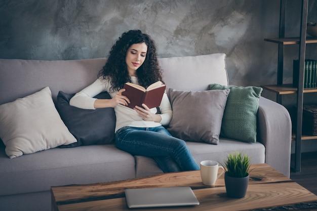 Portret ładnie wyglądającej uroczej słodkiej atrakcyjnej skoncentrowanej spokojnej dziewczyny siedzącej na kanapie i czytającej książkę w nowoczesnym loftowym stylu industrialnym salonie