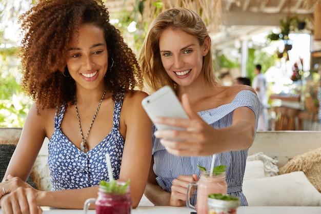 Portret ładnie wyglądających kobiet robi sobie selfie ze smartfonem, siada razem w kawiarni na świeżym powietrzu, spędza letnie wakacje za granicą, ciesząc się dobrym odpoczynkiem. ludzie, komunikacja i relacje