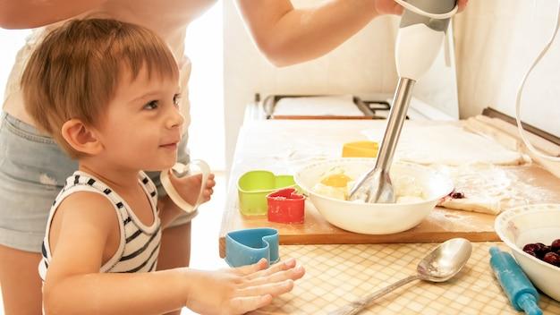 Portret ładny 3 lat chłopiec malucha gotowanie ciasteczek z matką. rodzinne gotowanie i pieczenie