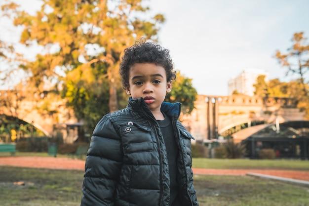Portret ładny afroamerykanin mały chłopiec stojący na zewnątrz w parku.
