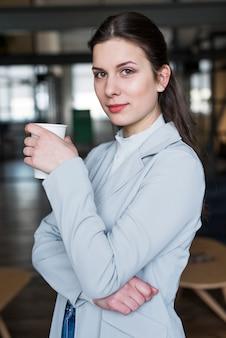 Portret ładny bizneswoman trzyma filiżankę