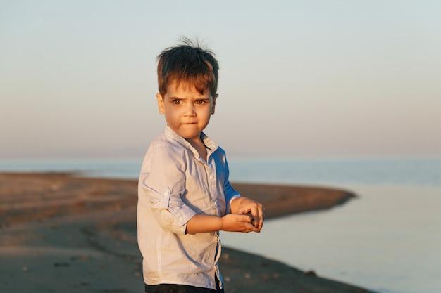 Portret ładny chłopiec 3 lat na plaży w oświetleniu zachód słońca.