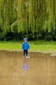 Portret ładny chłopiec bawi się ręcznie robionym statkiem. chłopiec z przedszkola żeglujący zabawkową łódką nad brzegiem wody w parku.