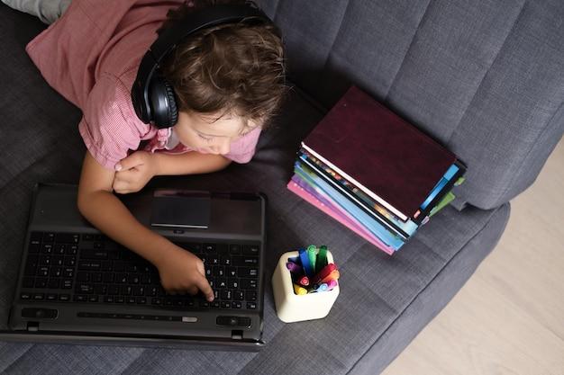 Portret ładny chłopiec kaukaski za pomocą laptopa i słuchawek podczas nauki w domu, koncepcja edukacji zdalnej. widok z góry. kwarantanna. powrót do koncepcji szkoły.