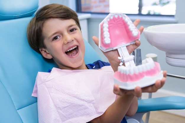 Portret ładny chłopiec trzymając pleśń dentystyczną