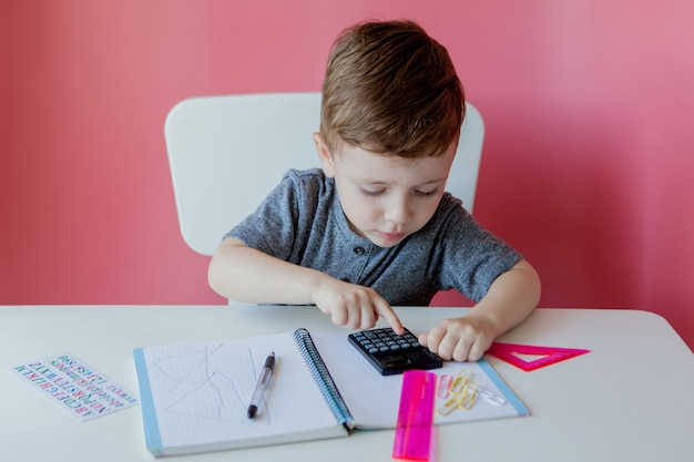 Portret ładny chłopiec w domu, dokonywanie pracy domowej. małe skoncentrowane dziecko piszące kolorowym ołówkiem w pomieszczeniu.