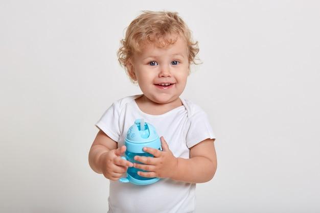 Portret ładny maluch trzymając butelkę wody, dziecko bawi się niebieskim kubkiem dla niemowląt