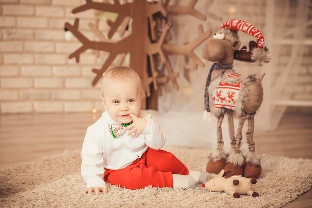 Portret ładny mały chłopczyk wśród ozdób choinkowych
