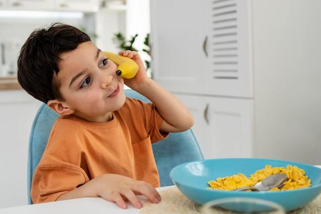 Portret ładny mały chłopiec bawi się bananem