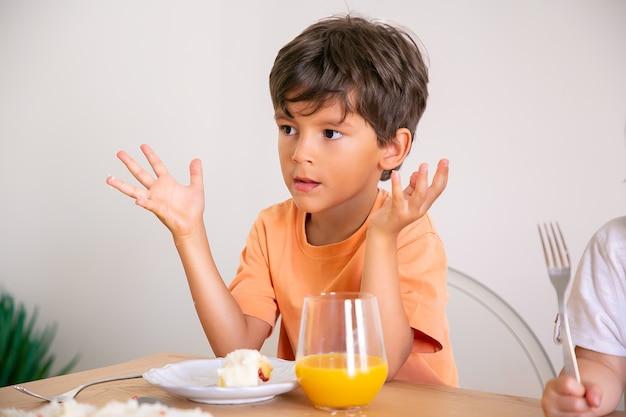 Portret ładny mały chłopiec jedzenie tort urodzinowy i picie soku pomarańczowego. urocze dziecko siedzi przy stole w jadalni, podnosząc ręce i odwracając wzrok. koncepcja dzieciństwa, uroczystości i wakacji
