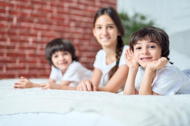 Portret ładny mały chłopiec łacińskiej uśmiecha się do kamery. brat spędza czas z rodzeństwem, leżąc na łóżku w domu. koncepcja szczęśliwe dzieci. selektywne skupienie