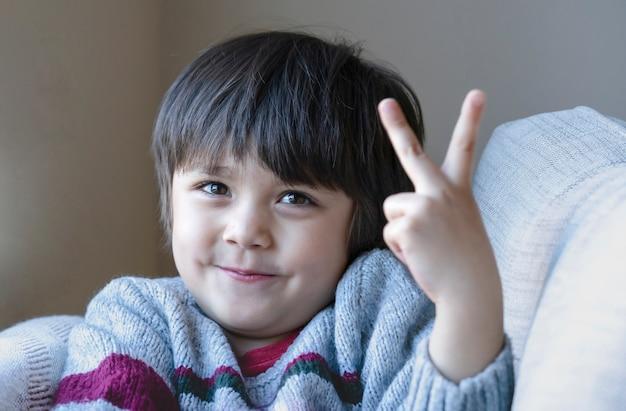Portret ładny mały chłopiec patrząc na aparat z uśmiechniętą twarzą, selektywne skupienie szczęśliwe dziecko pokazujące dwa palce