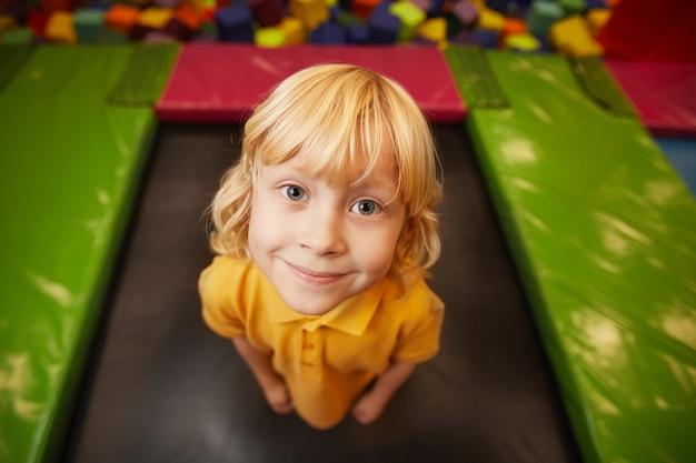 Portret ładny mały chłopiec patrząc z przodu podczas skakania na trampolinie w parku rozrywki