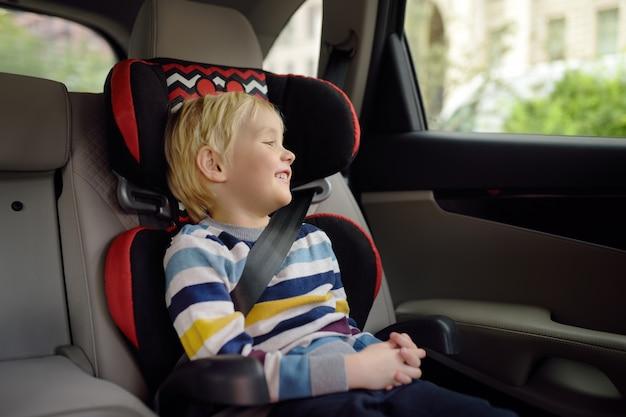 Portret ładny mały chłopiec siedzi w foteliku samochodowym. bezpieczeństwo transportu dzieci