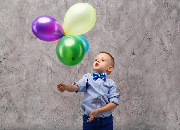 Portret ładny mały chłopiec w dżinsach, niebieskiej koszuli i muszce z wielobarwnymi balonami