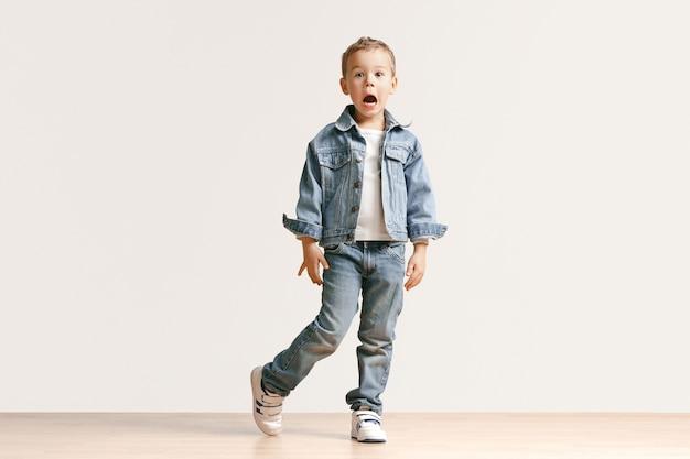 Portret ładny mały chłopiec w stylowe dżinsy, patrząc na kamery przed białą ścianą studio. koncepcja mody dla dzieci