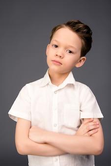 Portret ładny mały chłopiec z skrzyżowanymi rękami