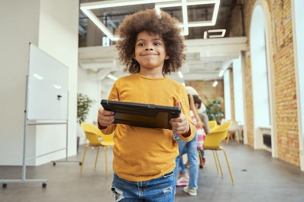 Portret ładny mały chłopiec z włosami afro uśmiechający się, trzymając i używając komputera typu tablet stojący w a