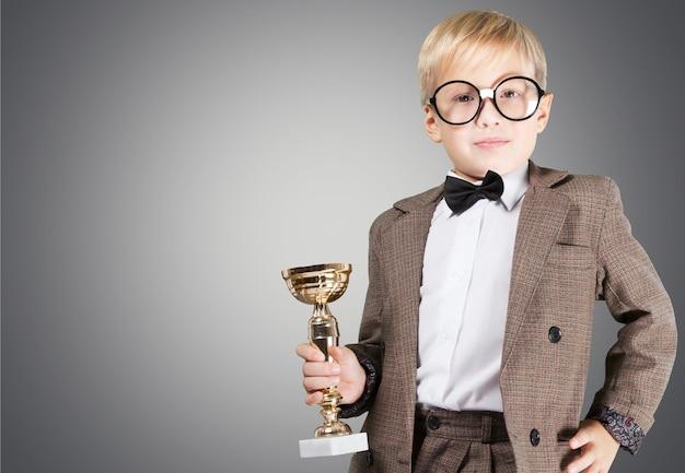 Portret ładny młody chłopak w okularach trzymający trofeum nad tłem