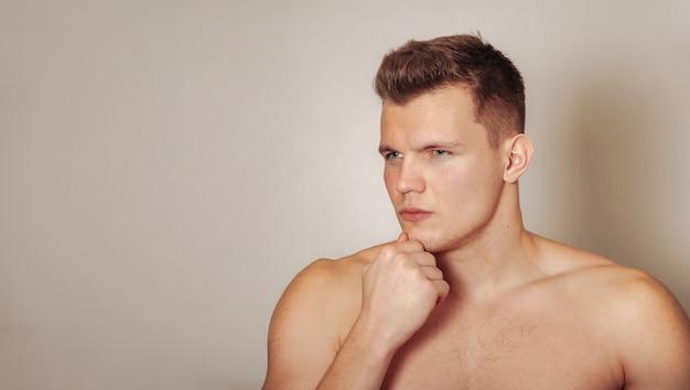 Portret ładny młody człowiek atletyczna budowa na jasnym tle na białym tle. przystojny, muskularny mężczyzna o dobrze umięśnionym ciele. pojęcie sportu, treningu na siłowni, fitness i zdrowego stylu życia. skopiuj miejsce