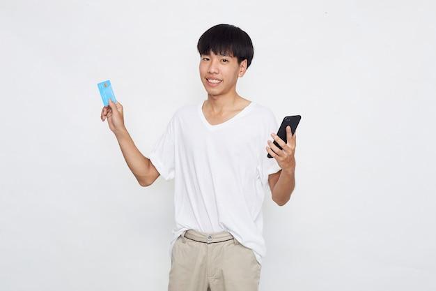 Portret ładny młody człowiek azjatyckich posiadający telefon komórkowy i pokazujący kartę kredytową na białym tle białej powierzchni
