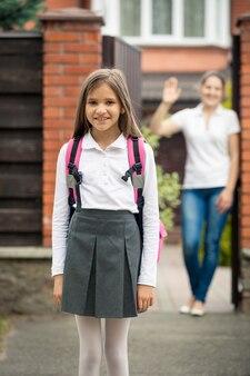Portret ładny uczennica stojący przed domem. matka macha stojąc w drzwiach