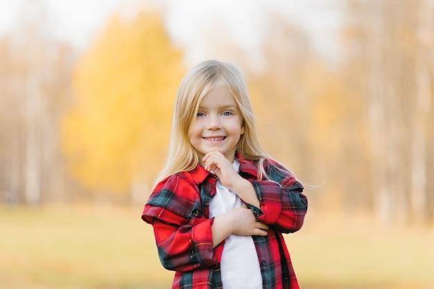 Portret ładny uroczy uśmiechnięta mała blondynka stojąca w jesiennym parku