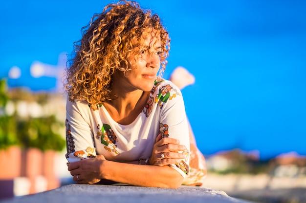 Portret ładny wesoły atrakcyjny model blondynka w średnim wieku położyć się i patrzeć na słońce podczas zachodu słońca w wakacje wypoczynek. zrelaksowany i swobodny styl życia. kręcone włosy piękna dziewczyna