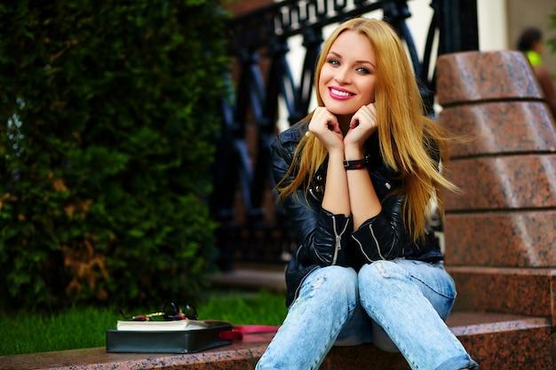 Portret ładny zabawny nowoczesny seksowny miejski młoda stylowa uśmiechnięta kobieta dziewczyna model w jasnym nowoczesnym suknem na zewnątrz siedzi w parku w dżinsach na ławce