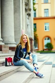 Portret ładny zabawny nowoczesny seksowny miejski młody stylowy uśmiechnięty kobieta dziewczyna model w jasnym nowoczesnym suknem na zewnątrz siedzi w mieście w dżinsach z różową torbą