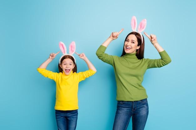 Portret ładnych, atrakcyjnych, uroczych, całkiem wesołych, wesołych dziewcząt ubranych w uszy królika, które bawią się na białym tle nad jasnym, żywym połyskiem, żywym niebieskim kolorem