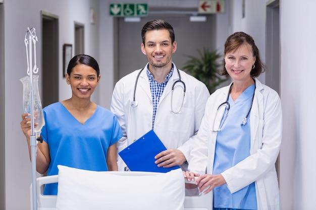 Portret lekarki i pielęgniarka stoi wpólnie łóżkiem szpitalnym