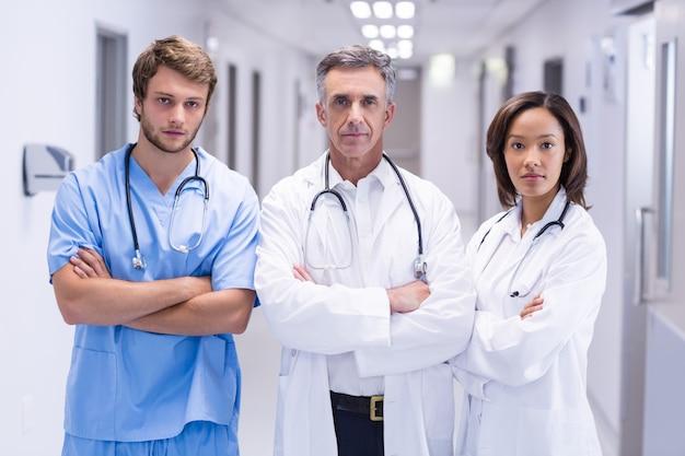 Portret lekarki stoi z rękami krzyżował w korytarzu