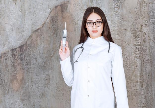 Portret lekarki trzymającej zastrzyk i patrzącej w kamerę na rustykalnej ścianie