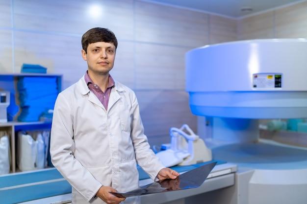 Portret lekarza. mężczyzna specjalista medyczny. chirurg lub radiolog, na tle sali medycznej.