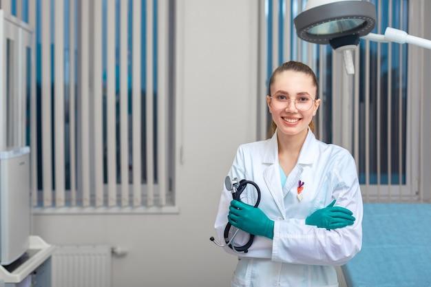 Portret lekarza patrząc w kamerę. młoda kobieta się uśmiecha. opieka zdrowotna, medyczna.