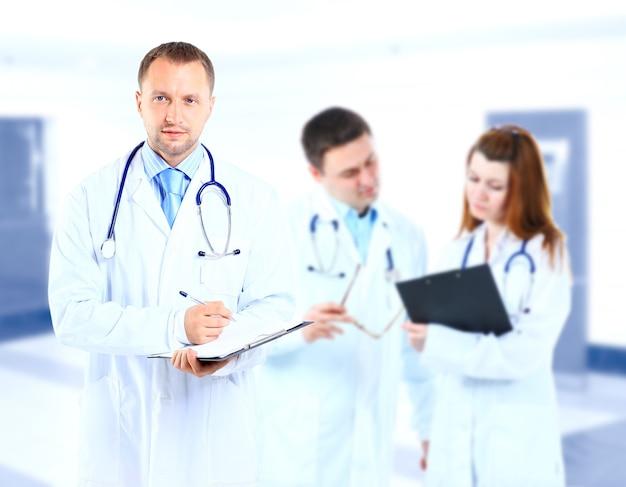 Portret lekarza uśmiechający się z kolegami w tle