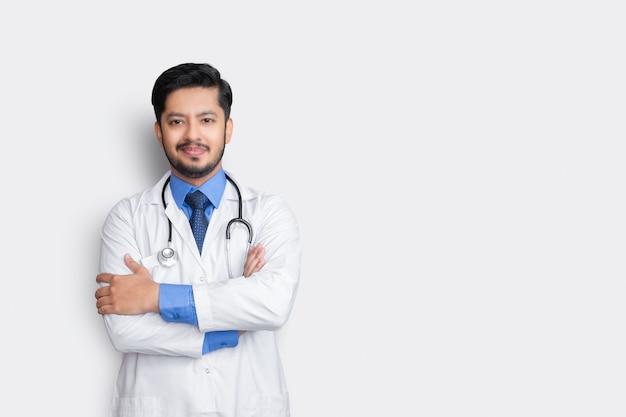 Portret lekarza z stetoskopem i ramieniem krzyż na białym tle na białej ścianie. koncepcja ubezpieczenia zdrowotnego.