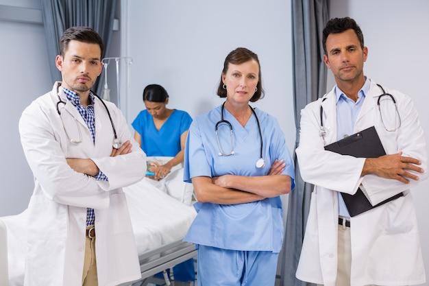 Portret lekarzy i pielęgniarki stały z rękami skrzyżowanymi