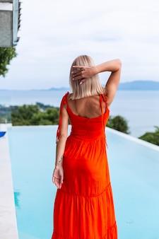 Portret luksusowo wyglądającej kobiety w czerwonej pomarańczowej sukni wieczorowej w bogatym hotelu