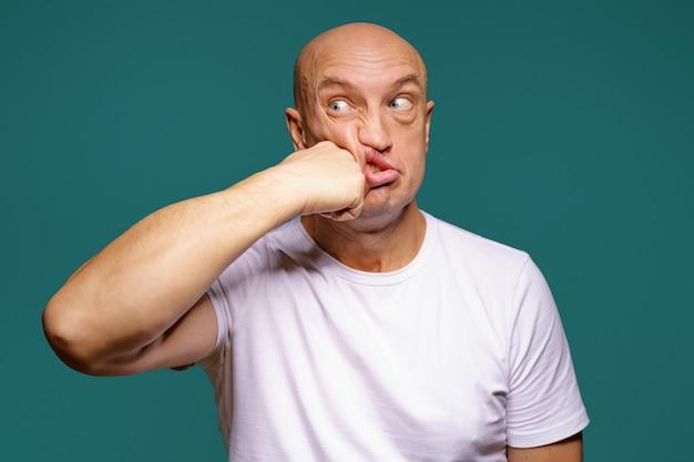 Portret łysego mężczyzny uderza się w policzek, wyraz twarzy