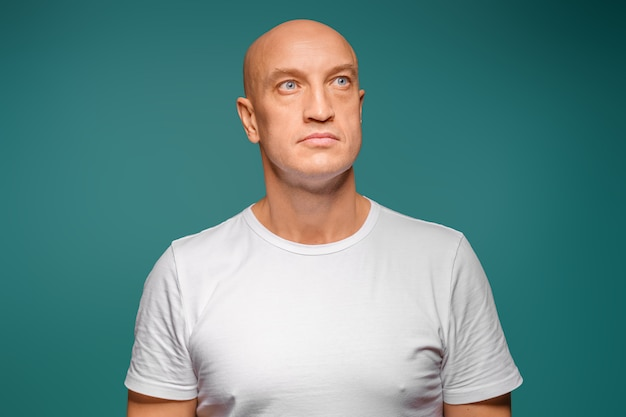 Portret łysego mężczyzny w białej koszulce na twarzy, wyraz twarzy