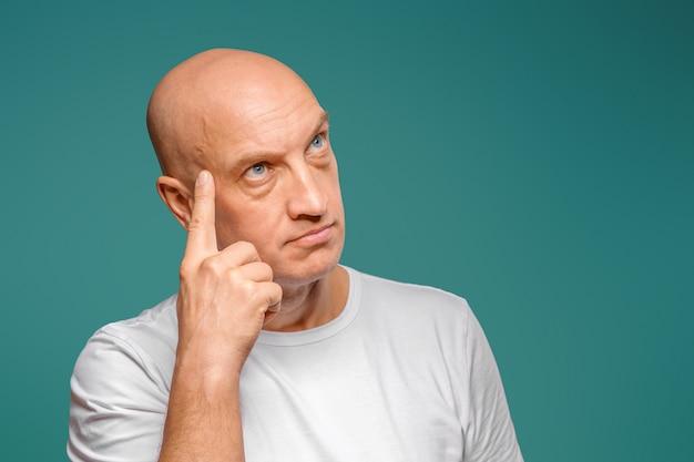 Portret łysego mężczyzny w białej koszulce w zamyślonym wyrazie, trzymającego palec przy skroni