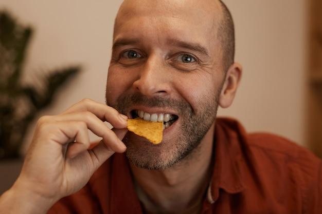 Portret łysiejący dojrzały mężczyzna jedzenie frytek
