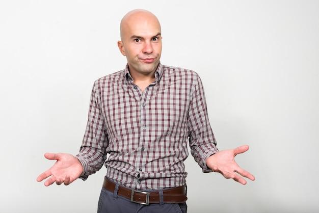 Portret łysy biznesmen wzruszając ramionami i patrząc zdezorientowany