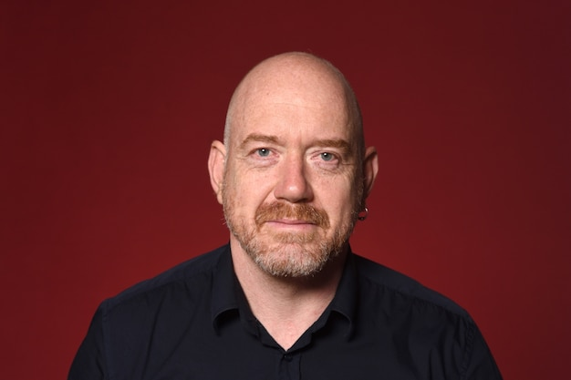 Portret łysy mężczyzna na czerwonym tle